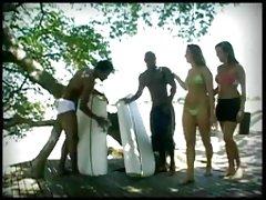 Dos chicas blancas con dos hombres de raza negra en la playa